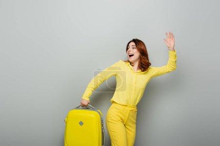 glückliche Frau, die wegschaut und winkt, während sie gelben Koffer auf grau hält