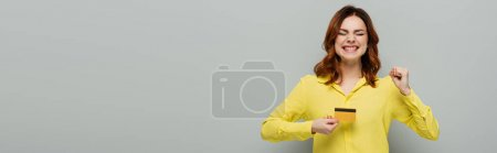 excited woman showing yes gesture while holding credit card on grey, banner