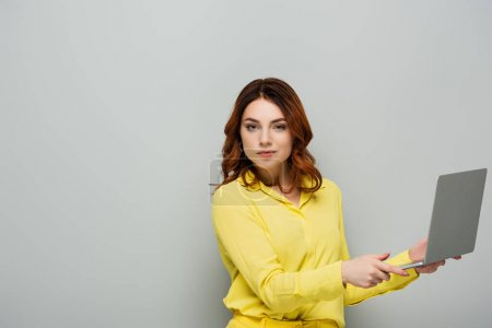 assured woman looking at camera while holding laptop on grey