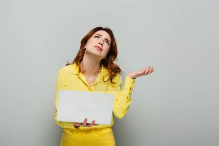upset woman looking up while standing with laptop on grey