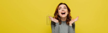 Photo for Cheerful woman looking up and gesturing isolated on yellow, banner - Royalty Free Image
