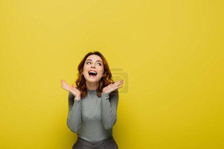 mujer feliz con el pelo ondulado mirando hacia otro lado mientras está de pie con las palmas abiertas en amarillo