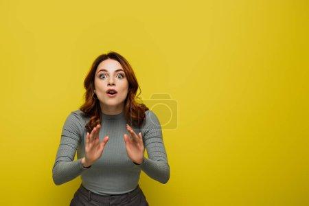 aufgeregte Frau im grauen Pullover gestikuliert, während sie in die Kamera auf gelb blickt