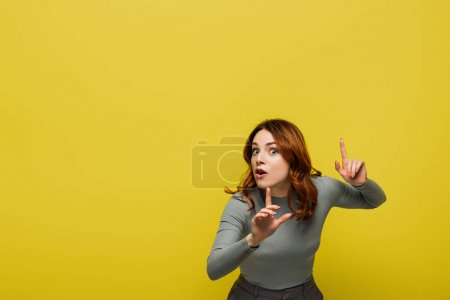 Photo for Woman with curly hair and open mouth pointing with fingers isolated on yellow - Royalty Free Image