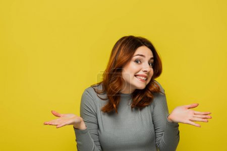 Photo for Smiling woman with wavy hair showing shrug gesture isolated on yellow - Royalty Free Image