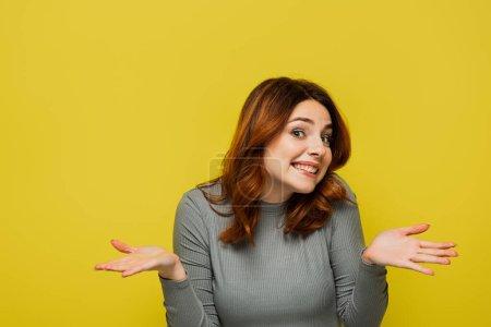 Lächelnde Frau mit welligem Haar zeigt achselzuckende Geste