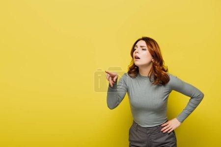 Photo pour Femme aux cheveux bouclés debout avec la main sur la hanche tout en pointant du doigt sur le jaune - image libre de droit