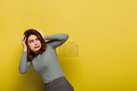 Photo pour Femme effrayée avec les cheveux bouclés regardant loin sur jaune - image libre de droit