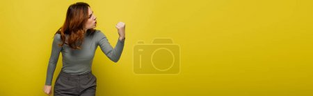 Photo for Angry woman with curly hair showing clenched fist on yellow, banner - Royalty Free Image
