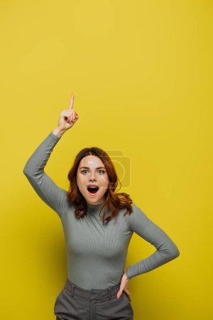 verblüffte Frau mit Idee und Blick auf Kamera auf gelb