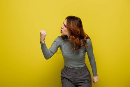 angry woman with curly hair showing clenched fist on yellow