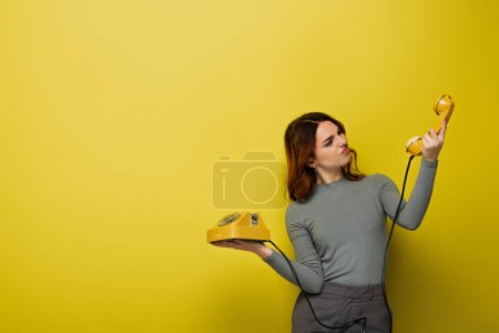 displeased young woman looking at retro phone on yellow