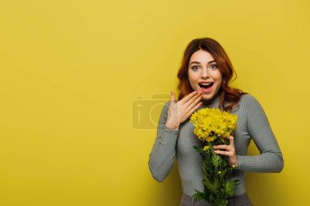 erstaunt Frau mit welligem Haar hält Blumen auf gelb