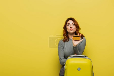 woman with curly hair pouting lips while holding baggage and credit card on yellow