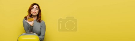 Photo for Woman with curly hair holding luggage and credit card isolated on yellow, banner - Royalty Free Image