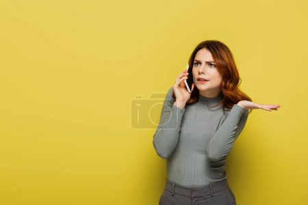 young displeased woman with curly hair talking on smartphone on yellow