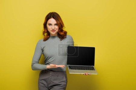 Foto de Mujer joven con el pelo rizado apuntando con la mano a la computadora portátil con pantalla en blanco en amarillo - Imagen libre de derechos