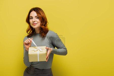 feliz joven mujer tirando de la cinta en el presente y sonriendo en amarillo