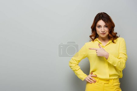 young curly woman in yellow shirt standing with hand on hip and pointing with finger on grey