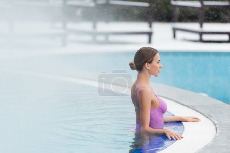 Photo for Side view of young woman in swimsuit bathing in outdoor swimming pool - Royalty Free Image