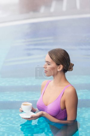 Photo for Young woman in swimsuit holding cup of coffee and saucer in outdoor swimming pool - Royalty Free Image