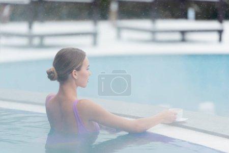 junge Frau greift im Freibad nach einer Tasse Kaffee