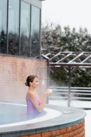 heureuse jeune femme en maillot de bain tenant tasse de café et souriant dans la piscine extérieure