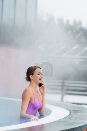 happy woman in swimsuit talking on smartphone while laughing and bathing in outdoor swimming pool