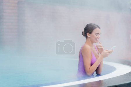 happy woman in swimsuit holding smartphone while bathing in outdoor swimming pool in spa center