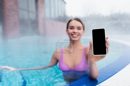 Photo for Blurred and cheerful woman holding smartphone with blank screen while bathing in outdoor pool - Royalty Free Image