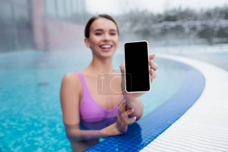 cheerful woman holding smartphone with blank screen while bathing in outdoor swimming pool