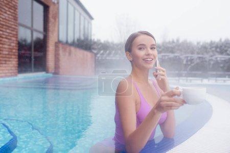 fröhliche junge Frau beim Baden im Thermalfreibad mit Smartphone und Becher