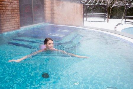 jeune femme souriant tout en nageant dans la piscine extérieure de source chaude