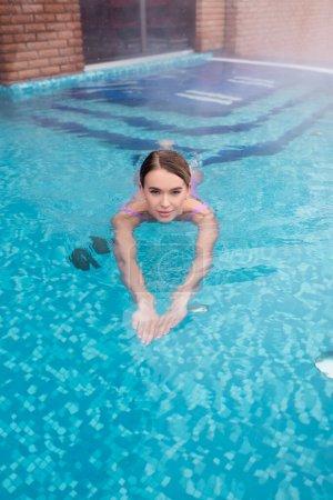 young woman bathing in outdoor swimming pool with blue water