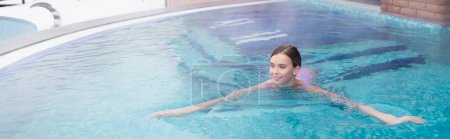 happy young woman swimming in hot spring pool, banner