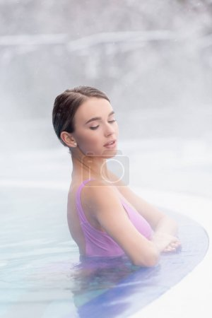 steam near young woman bathing in outdoor hot spring pool