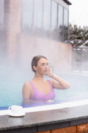vapor cerca de la mujer joven mirando hacia otro lado y nadando en la piscina termal al aire libre cerca de la taza en primer plano borrosa