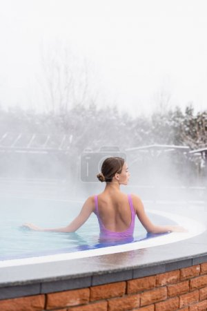 steam near young woman looking away while taking bath in outdoor hot spring pool
