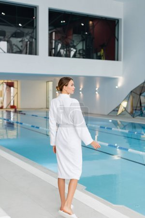 full length of young woman in white bathrobe standing near pool in spa center