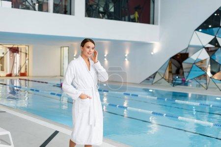 mujer joven en albornoz blanco caminando con la mano en el bolsillo cerca de la piscina en el centro de spa