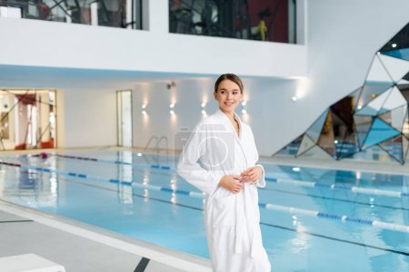 happy young woman in white bathrobe standing near pool in spa center