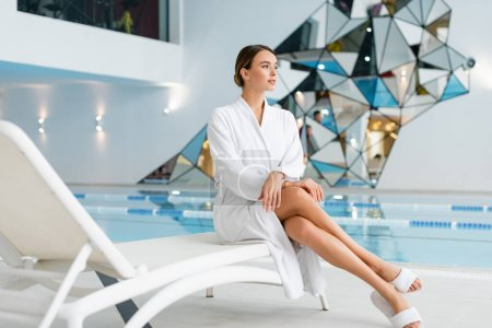 full length of young woman in white bathrobe sitting on deck chair in spa center