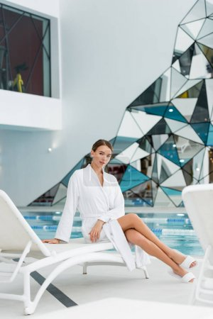 longitud completa de la mujer joven en albornoz sentado en la silla de cubierta en el centro de spa