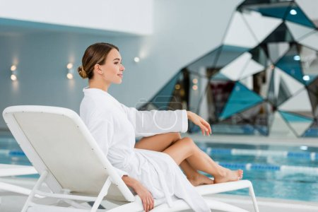 full length of pleased young woman in white bathrobe resting on deck chair near pool