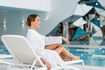longitud completa de la joven complacida en albornoz blanco descansando en la silla de cubierta cerca de la piscina
