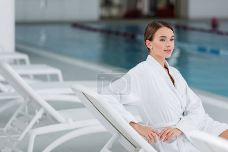 young woman in white bathrobe resting on deck chair near pool
