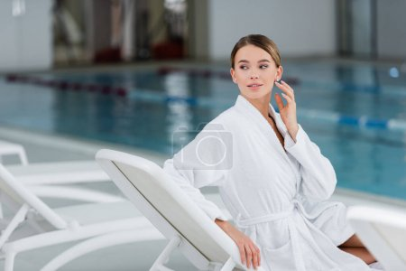 young woman in white bathrobe looking away while resting on deck chair near pool
