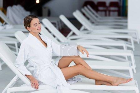mujer alegre en albornoz blanco descansando en la silla de cubierta en el centro de spa