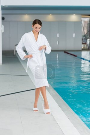 full length of happy young woman adjusting bathrobe near pool