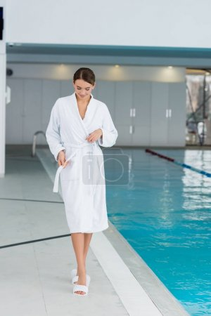 Photo for Full length of cheerful young woman adjusting bathrobe near pool - Royalty Free Image